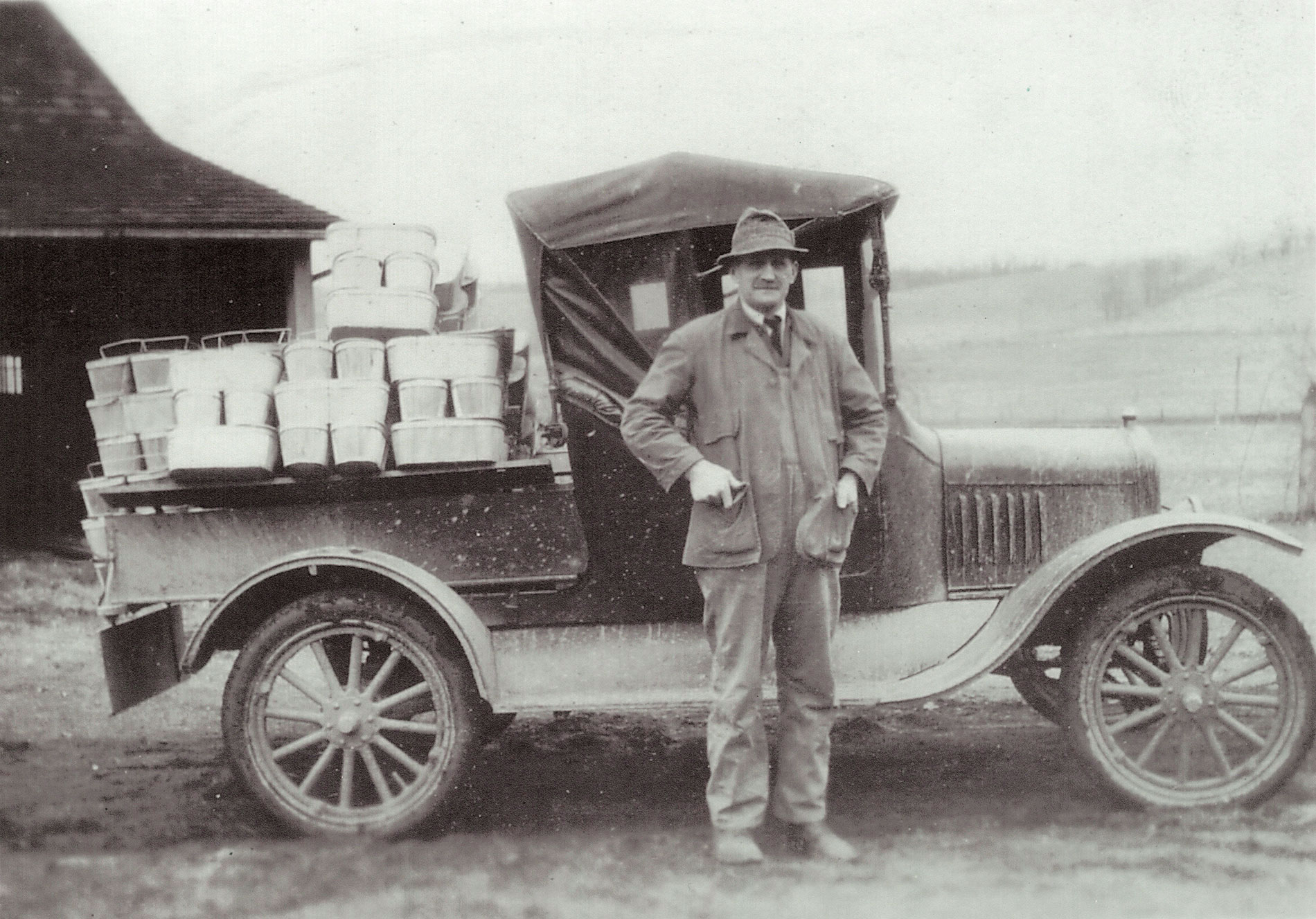 Old black and white photo of farmer standing in front of a truck loaded with Mother Earth mushrooms